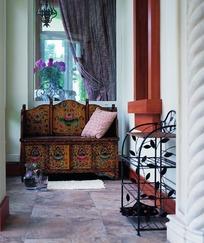 精美图案柜子上的粉色抱枕和黑色铁艺鞋架