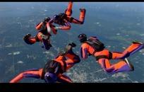 极限运动视频 城市上空跳伞的橙色衣服的运动员