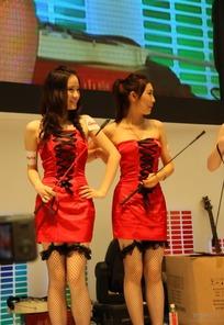 游戏展抹胸露肩红色连身裙拿着马鞭的两个美女