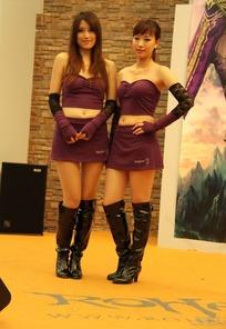 游戏展舞台上紫色短裙抹胸露脐服饰的性感美女