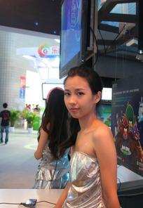 游戏展舞台前银色抹胸露肩的美女侧身