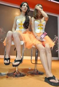 游戏展两个坐在舞台椅子休息的露肩低胸的美女
