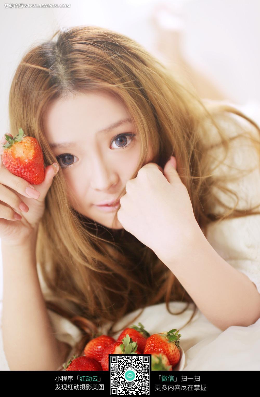 手拿草莓趴着的美女