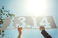 情侣各用一只手举起1314的牌子
