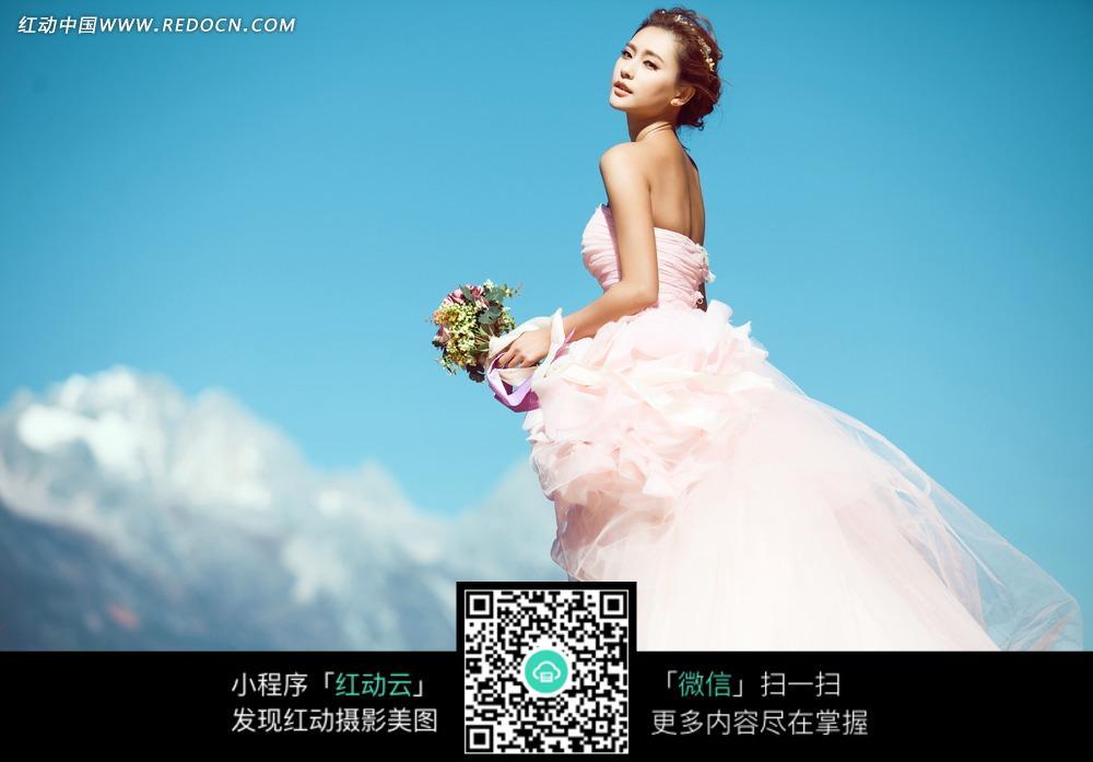 拿着鲜花回眸的美女婚纱摄影图片