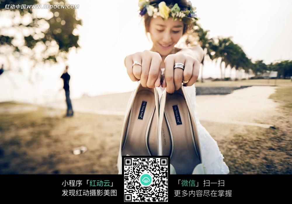 拿着鞋子的美女婚纱摄影图片