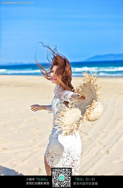 沙滩上手拿草帽的美女