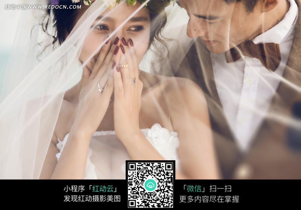 捂嘴的美女和伴侣婚纱摄影图片