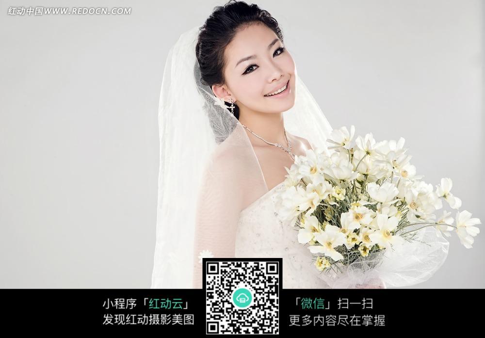 手拿鲜花微笑的美女婚纱摄影