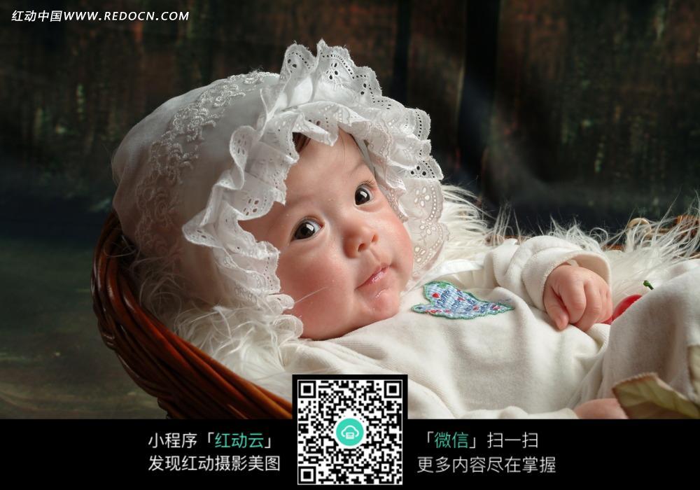 戴睡帽躺在篮子里的宝宝图片