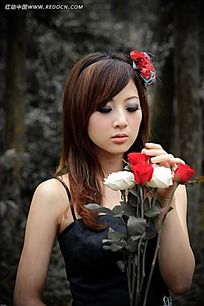 摘树叶的美女写真摄影图片