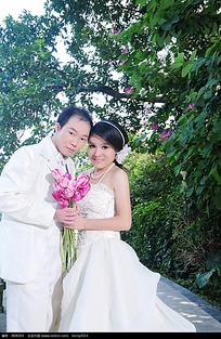树林里双手捧花的新郎新娘