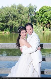 在大桥上湖边相拥的新郎新娘