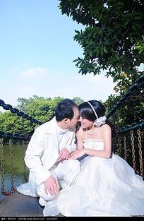 在吊桥上亲吻的新郎新娘