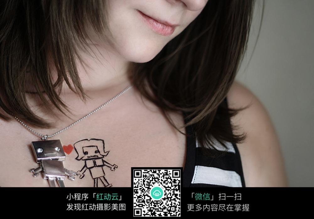 女人的卡通人物项链和胸口纹身特写jpg图片