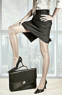 右脚踩在公文包上的女人腿部特写JPG