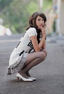 蹲在地上的长卷发美女街拍
