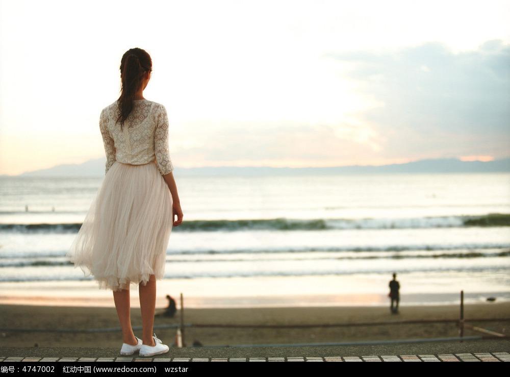 马尾女孩白色纱裙海边背影图