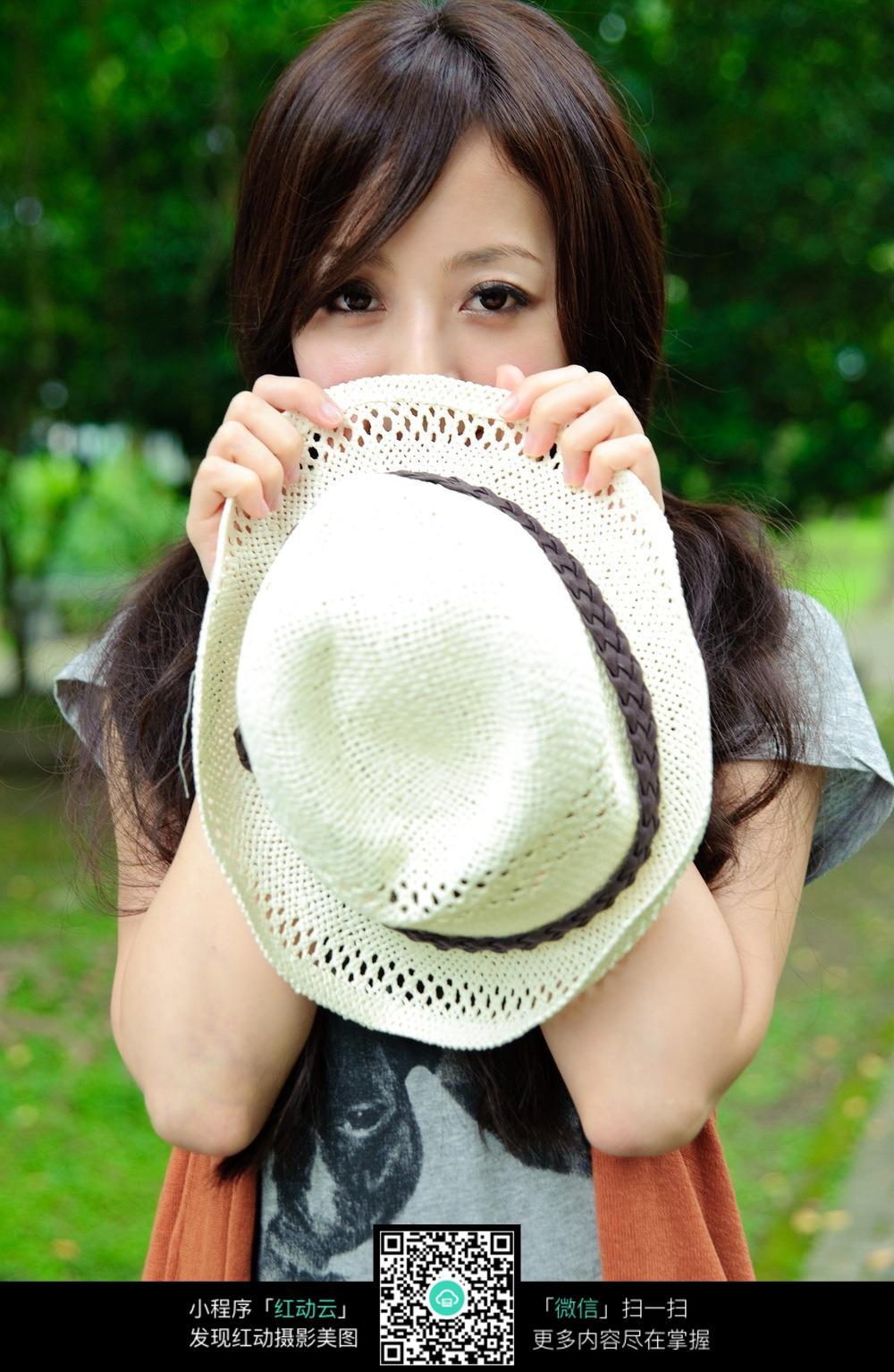 拿着帽子半遮脸的女孩