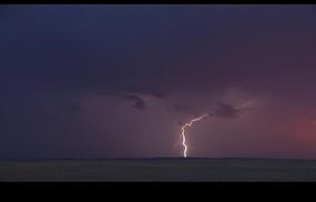 自然天气片段 大海上紫色积雨云的电弧闪光