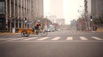 环卫工人骑自行车路过马路视频